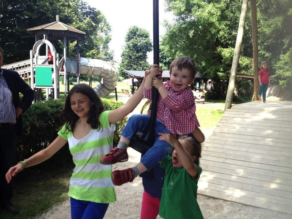 Kleinkind spielt mit Kindern auf Seilrutsche im Tierpark Rosegg