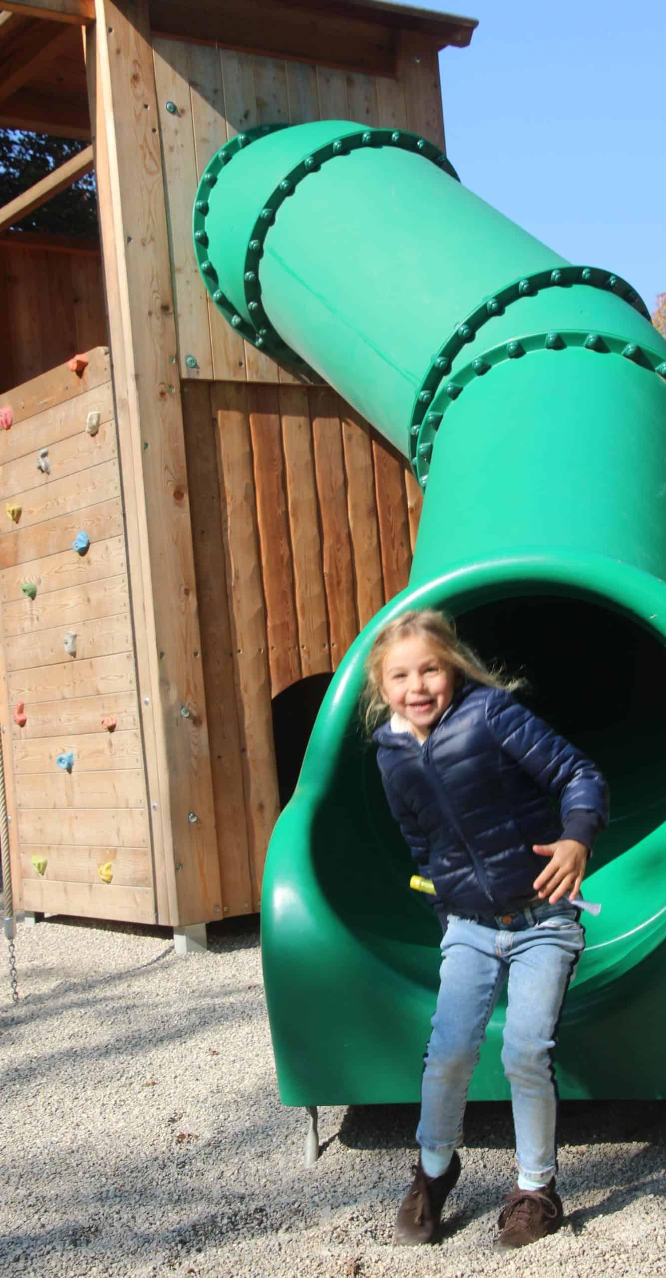 Kind auf Rutsche im Tierpark bei Familienausflug in Kärnten